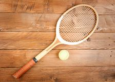 Raquet and in wood background. Raquet and ball in wood background royalty free stock images