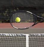 Raqueta con la pelota de tenis en corte Fotos de archivo
