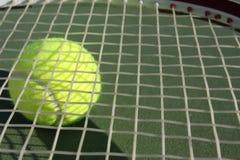 Raqueta de tenis con una pelota de tenis debajo Fotografía de archivo