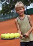 Raqueta de tenis de la explotación agrícola del muchacho con las bolas Imagen de archivo