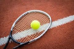 Raqueta y bola de tenis en corte Foto de archivo