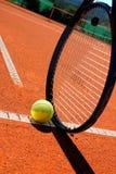 Raqueta y bola de tenis en el campo de tenis Fotografía de archivo libre de regalías