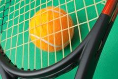 Raqueta y bola de tenis en fondo verde Fotografía de archivo libre de regalías