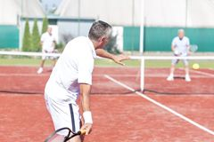 Raquete de balanço do homem ao jogar dobros do tênis na corte vermelha durante o fim de semana do verão fotografia de stock royalty free