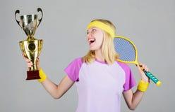 Raquete de tênis atlética da posse da menina e cálice dourado Jogo do tênis da vitória Equipamento do esporte do desgaste de mulh foto de stock