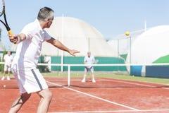 A raquete de tênis de balanço do homem ao jogar dobros combina na corte vermelha durante o fim de semana do verão foto de stock