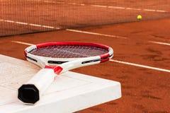 Raquete de tênis na tabela, na corte de argila, na rede e na bola Imagens de Stock Royalty Free