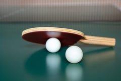 Raquete do t?nis de mesa e duas bolas em uma tabela verde Rede do t?nis de mesa imagem de stock royalty free