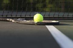 Raquete e bola de tênis pela rede Fotografia de Stock Royalty Free