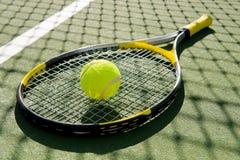 Raquete e esfera de tênis na corte