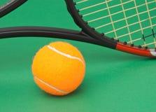 Raquete e esfera de tênis no fundo verde Imagem de Stock Royalty Free