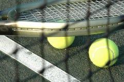 Raquete e esferas através da rede Fotografia de Stock Royalty Free