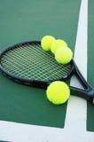 Raquete e esferas de tênis na corte fotografia de stock
