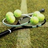 Raquetes de tênis com as bolas na corte da superfície dura Imagem de Stock
