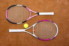 Raquetes de tênis com bola em uma corte de argila fora Imagem de Stock Royalty Free