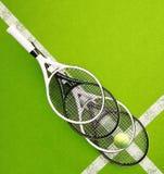 Raquetes de tênis com a bola na corte da superfície dura quadrado Vagabundos do tênis Imagem de Stock