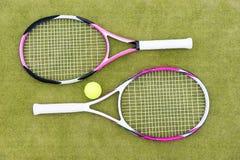 Raquetes de tênis com a bola no fundo verde Foto de Stock Royalty Free