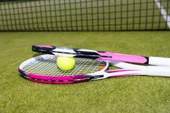 Raquetes de tênis cor-de-rosa desportivas com a bola no fundo verde Imagem de Stock