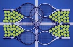 Raquetes de tênis desportivas com as bolas no fundo azul Fotografia de Stock
