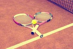Raquetes de tênis desportivas com a bola no fundo cor-de-rosa Fotografia de Stock