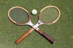 Raquetes de tênis do vintage e bola de tênis branca antiga no campo de tênis da grama Imagens de Stock