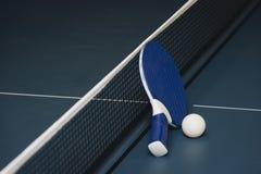 Raquetes de tênis de mesa e bola e rede em uma tabela de pingpong azul fotos de stock royalty free