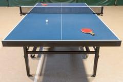 Raquetes e bola de tênis de mesa em uma tabela Fotografia de Stock