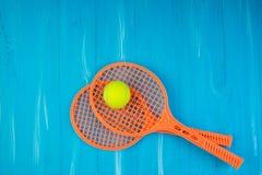 Raquetes e bola de tênis no fundo de madeira azul imagem de stock