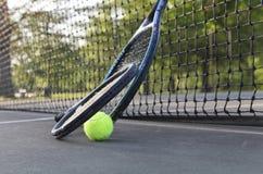 Raquetes e bola de tênis que inclinam-se na rede Foto de Stock Royalty Free