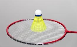 Raquetes e petecas de badminton no branco imagem de stock