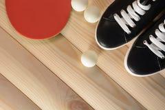 Raquette de ping-pong, boules et espadrilles noires avec les dentelles blanches sur un fond en bois Image libre de droits