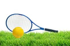 Raquette de tennis bleue et balle de tennis jaune sur l'isolat d'herbe verte Image stock