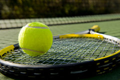 Raquette et bille de tennis sur la cour Photos stock