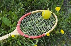 Raquette et boule de tennis sur l'herbe et les pissenlits Image libre de droits