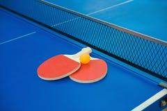 Raquettes de ping-pong et boule et filet sur la table de ping-pong bleue Image libre de droits