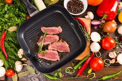 Rare Beef Slices in Pan Surrounded by Ingredients royalty free stock images