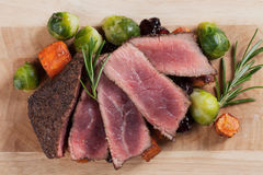 Rare beef steak with carrot and brussel sprout Royalty Free Stock Images