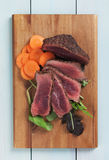 Rare beef steak with carrot and rocket salad Royalty Free Stock Image