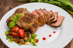 Rare Beef steak medium grilled with barbecue sauce. Wooden table. Top view. Close-up. Rare Beef steak medium grilled with barbecue sauce. Wooden table. Top view Stock Image