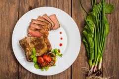 Rare Beef steak medium grilled with barbecue sauce. Wooden table. Top view. Close-up. Rare Beef steak medium grilled with barbecue sauce. Wooden table. Top view Royalty Free Stock Image