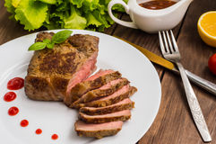 Rare Beef steak medium grilled with barbecue sauce. Wooden table. Top view. Close-up. Rare Beef steak medium grilled with barbecue sauce. Wooden table. Top view Stock Photos
