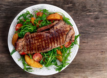 Rare beef steak with roasted potatoes, tomatoes, wild rocket leaves. Royalty Free Stock Photo