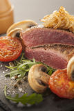 Rare beef steak. With tomato and mushrooms Stock Photography