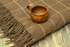 Antique old clay cup and warm, soft woolen plaid on dark natural wooden background stock photos