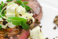 Rare cooked steak with capers and cheese topping Royalty Free Stock Photo