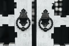 Rare door knobs on wooden gates. Beautiful handles on unusual gate in black and white Stock Image