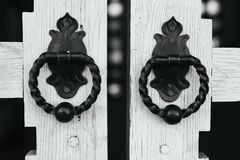 Rare door knobs on wooden gates. Beautiful handles on unusual gate in black and white Stock Images
