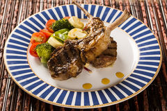 Rare fried rack of lamb with vegetables. Royalty Free Stock Images