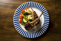 Rare fried rack of lamb with vegetables. Royalty Free Stock Photo