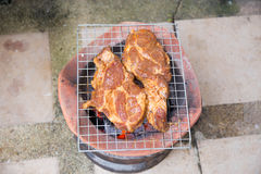 Rare pork grilled on charcoal brazier. Rare pork on stove outdoor Royalty Free Stock Images